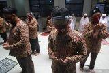 Sejumlah guru berdoa usai melaksanakan shalat ghaib saat penutupan Masa Pengenalan Lingkungan Sekolah (MPLS) di SD Muhammadiyah 11, Surabaya, Jawa Timur, Rabu (15/7/2020). Penutupan MPLS di sekolah tersebut diisi dengan pelaksanaan shalat ghaib untuk mendoakan salah satu wali murid yang meninggal akibat COVID-19 dan penerbangan balon dengan harapan wabah COVID-19 segera berlalu. Antara Jatim/Moch Asim/zk.