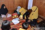 Guru Taman kanak kanak (TK) Rumah Anak Nanggroe Aceh (kanan) melaksanakan proses belajar mengajar kepada murid dari keluarga duafa yang tinggal di barak penampungan bekas tsunami, Desa Punge Blang Cut, Banda Aceh, Selasa (21/7/2020). Untuk keberlangsung pendidikan anak usia dini yang terdampak pandemi COVID-19, sejumlah guru TK Ruman Aceh itu melaksanakan metode pembelajaran dengan mendatangi sebanyak 60 rumah warga duafa, di barak penampungan maupun di rumah sewa, karena mereka tidak memiliki handphone atau laptop untuk belajar secara daring. Antara Aceh/Ampelsa.