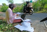 Seorang mahasiswa jurusan manajemen Universitas Muhammadiyah Magelang Teara Noviani (kiri) mengerjakan Ujian Tengah Semester secara daring di pinggir jalan kawasan pegunungan Menoreh di Desa Kenalan, Borobudur, Magelang, Jawa Tengah, Senin (20/7/2020). Teara mengaku kesulitan mendapatkan sinyal internet di wilayahnya, sehingga setiap hari terpaksa mengerjakan tugas kuliah dan ujian di pinggir jalan yang sinyal internetnya kuat. ANTARA FOTO/Anis Efizudin/wsj.