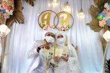 Pasangan pengantin menggunakan masker dan menunjukkan buku nikah saat resepsi pernikahan di Perumahan Grand Sutera Leuwiliang, Kabupaten Bogor, Jawa Barat, Rabu (22/7/2020). Pemerintah Kabupaten Bogor mengijinkan resepsi pernikahan dan selamatan khitanan dengan sejumlah syarat protokol kesehatan COVID-19 serta pembatasan jumlah tamu undangan saat penerapan PSBB Adaptasi Kebiasaan Baru atau Pra-AKB. ANTARA FOTO/Arif Firmansyah/pras.