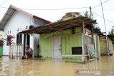 Seorang warga duduk di depan rumahnya yang terendam air luapan Sungai Bone di Ipilo, Kota Gorontalo, Gorontalo, Jumat (24/7). Intensitas hujan yang tinggi mengakibatkan meluapnya Sungai Bone dan merendam ratusan rumah di dua Kecamatan yaitu Dumbo Raya dan Kota Timur. (ANTARA FOTO/Adiwinata Solihin)