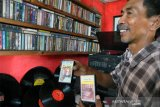 Penjual menunjukkan koleksi kaset pita musik jadul di Terminal Musik Djadoel, Cibungbulang, Kabupaten Bogor, Jawa Barat, Selasa (21/7/2020). Ratusan kaset pita dan piringan hitam musik jadul di era tahun 60 hingga 70an karya musisi Indonesia maupun mancanegara tersebut masih diminati penggemarnya di tengah musik modern. (ANTARA FOTO/Arif Firmansyah).