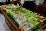 Personil Polda Aceh menata sejumlah barang bukti tindak kejahatan narkoba jenis sabu yang dikemas dalam bungkusan teh saat gelar kasus di Banda Aceh, Senin (27/7/2020). Tim gabungan Polda Aceh bersama Bea Cukai menggagalkan peredaran narkoba jenis sabu sebanyak 33 bungkus dengan total seberat 33 kilogram jaringan internasional yang diselundupkan dari Malaysia melalui jalur laut menggunakan kapal nelayan di perairan Lhokseumawe, Aceh Utara dan mengamankan empat tersangka. Antara Aceh/Ampelsa.