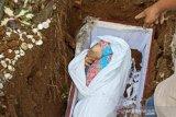 Viral foto jenazah COVID-19 dikubur masih pakai baju daster dilapis kain kafan