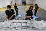 Sejumlah petugas Kepolisian merapikan barang bukti narkotika jenis sabu usai rilis di gudang penyimpanan daerah Cikarang, Kabupaten Bekasi, Jawa Barat, Rabu (29/7/2020). Penyelundupan sabu sebanyak 200 kg oleh jaringan internasional dari Myanmar tersebut bermodus menyembunyikan sabu dalam karung berisi jagung yang tersebar di tiga wilayah Cikarang, Jakarta, dan Bangka Belitung. ANTARA FOTO/ Fakhri Hermansyah/nym.