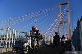 Pengendara motor melintasi Jembatan Suramadu, Surabaya, Jawa Timur. Kamis (30/7/2020). Menjelang Hari Raya Idul Adha 1441 H, jembatan penghubung antara Pulau Jawa dengan Pulau Madura tersebut dipadati kendaraan khususnya pemudik yang menggunakan motor menuju Pulau Madura. Antara Jatim/Zabur Karuru