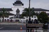 Petugas keamanan duduk sambil berjaga di depan Gedung Sate, Bandung, Jawa Barat, Kamis (30/7/2020). Sebanyak 40 karyawan di Gedung Sate atau Kantor Gubernur Jawa Barat terkonfirmasi positif  COVID-19 melalui uji tes usap (swab test) sehingga selama 14 hari Gedung Sate ditutup untuk publik dan aktivitas Pegawai Negeri Sipil serta non pegawai di lingkungan tersebut bekerja dari rumah. ANTARA JABAR/Novrian Arbi/agr