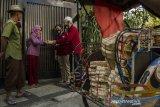 Pengurus Dewan Kemakmuran Masjid (DKM) membagikan daging kurban menggunakan besek (wadah anyaman bambu) kepada warga di kawasan Cihapit, Bandung, Jawa Barat, Jumat (31/7/2020). Pengurus DKM menggunakan besek untuk mengemas daging kurban seberat satu kilogram guna mengurangi sampah plastik serta membagikan kepada warga penerima secara langsung dari rumah ke rumah sebagai penerapan protokol kesehatan pada masa Adaptasi Kebiasaan Baru pandemi COVID-19 di Hari Raya Idul Adha. ANTARA JABAR/Novrian Arbi/agr