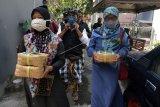 Anggota Pecalang atau petugas keamanan adat Bali mendampingi umat Islam saat mengantarkan daging kurban ke rumah warga umat Hindu pada Hari Idul Adha 1441 H di Denpasar, Bali, Jumat (31/7/2020). Pembagian daging kurban ke masing-masing rumah warga tersebut untuk mencegah kerumunan dengan menerapkan protokol kesehatan COVID-19 dan untuk tetap mempertahankan toleransi antarumat beragama. ANTARA FOTO/Nyoman Hendra Wibowo/nym.