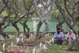 Warga melakukan ziarah kubur saat Hari Raya Idul Adha di Pemakaman Muslim Wanasari, Denpasar, Bali, Jumat (31/7/2020). Pengurus pemakaman tersebut mengizinkan warga untuk melakukan ziarah saat Hari Raya Idul Adha dengan menerapkan sejumlah protokol kesehatan seperti wajib mengenakan masker, mencuci tangan dan menjaga jarak antar peziarah untuk mengantisipasi penyebaran COVID-19. ANTARA FOTO/Fikri Yusuf/nym.