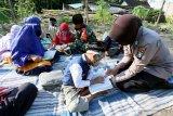Polwan Polres Blitar Kota Bripka Anissa Saraswati (Kanan) bersama Babinsa Kodim/0808 Blitar Serka Hajib (Dua Kanan) mengajar mengaji sejumlah santri dan santriwati Madrasah Diniyah di salah satu lahan milik warga di Kelurahan Tanggung, Blitar, Jawa Timur, Sabtu (1/8/2020). Bripka Anissa dan Serka Hajib berinisiatif melakukan kegiatan belajar mengajar secara darurat di lahan milik warga, akibat madrasah diniyah tempat sejumlah santri itu mengaji menghentikan kegiatannya sejak memasuki masa Pandemi COVID-19 pada Maret lalu, dan kegiatan belajar mengaji tidak memungkinkan dilakukan secara daring. Antara Jatim/Irfan Anshori/zk