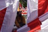 Pedagang musiman bendera dan hiasan bernuansa merah putih menunggu pembeli di Kota Madiun, Jawa Timur, Senin (3/8/2020). Puluhan pedagang musiman berjualan bendera, umbul-umbul dan hiasan bernuansa merah putih yang dijual dengan harga antara Rp15 ribu hingga Rp350 ribu per lembar selama menjelang peringatan HUT ke-75 Proklamasi Kemerdekaan RI. Antara Jatim/Siswowidodo/zk.