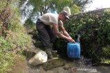Seorang warga Sungai Jambu menampung air yang mengalir dari sumber mata air di kaki Gunung Kerinci, Kayu Aro Barat, Kerinci, Jambi, Minggu (2/8/2020). Beberapa desa yang wilayahnya belum mendapatkan layanan Perusahaan Daerah Air Minum (PDAM) di daerah itu memanfaatkan sumber mata air di kaki Gunung Kerinci untuk kebutuhan sehari-hari. ANTARA FOTO/Wahdi Septiawan/aww.