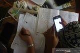 Sejumlah siswa mengikuti proses belajar mengajar dalam jaringan (daring) di bekas posko COVID-19 di tepi jalan untuk mendapatkan sinyal jaringan internet di Desa Madang, Kabupaten Hulu Sungai Selatan, Kalimantan Selatan, Selasa (4/8/2020). Siswa sekolah di pelosok Kalimantan Selatan masih kesulitan untuk mengikuti proses belajar mengajar daring selama masa pandemi COVID-19 akibat sulitnya akses internet di daerah itu. Foto Antaranews Kalsel/Bayu Pratama S.