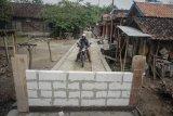 Seorang pengendara melintas jalan kampung yang ditutup dengan tembok di Desa Gading, Tanon, Sragen, Jawa Tengah, Selasa (4/8/2020). Penutupan jalan tersebut dipicu perselisihan warga dengan pemilik tanah yang merasa tidak diajak bermusyawarah saat pembangunan jalan kampung. ANTARA FOTO/Mohammad Ayudha/hp.