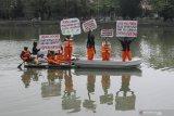 Sejumlah aktivis lingkungan yang tergabung dalam Ecoton membentangkan poster diatas perahu di Sungai Surabaya, Jawa Timur, Rabu (5/8/2020). Aksi itu guna menyadarkan masyarakat agar tidak membuang sampah khususnya sampah plastik ke sungai yang berakibat membahayakan kehidupan biota sungai. Antara Jatim/Didik/Zk