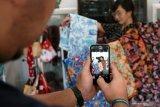 Pengrajin batik khas blitar Yogi Rosdianta memotret istrinya Santika sambil memegang batik hasil produksinya menggunakan gawai untuk diunggah ke pasar digital di sentra kerajinan batik khas Blitar Mawar Putih, di Blitar, Jawa Timur, Rabu (5/8/2020). Pengrajin batik khas Blitar tersebut mengaku mulai mengalami kenaikan omzet hingga menemukan peluang pembukaan pangsa pasar baru, dengan memanfaatkan pasar digital (Marketplace) hingga media sosial daring, setelah sebelumnya sempat mengalami penurunan omzet hingga 70 persen, saat pandemi COVID-19. Antara Jatim/Irfan Anshori/zk.