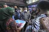 Menteri Dalam Negeri Tito Karnavian (dua kanan) bersama Gubernur Jawa Barat Ridwan Kamil (dua kiri) melihat pembuatan KTP elektronik saat kunjungan kerja di Indramayu, Jawa Barat, Rabu (5/8/2020). Kunjungan kerja mendagri tersebut dalam rangka peluncuran Gerakan Sejuta Masker sekaligus mengecek kesiapan dan pemantapan penyelenggaraan pilkada serentak pada Desember 2020. ANTARA JABAR/Dedhez Anggara/agr