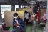 Penumpang berada di dalam Kereta Api (KA) Sri Tanjung jurusan Yogyakarta-Banyuwangi Jawa Timur saat transit di Stasiun KA Madiun, Jawa Timur, Jumat (7/8/2020). Selama masa pandemi COVID-19 PT KAI Daerah Operasi (Daop) 7 Madiun mencatat terjadi lonjakan jumlah penumpang yang naik dan turun di seluruh stasiun di daerah itu hingga 94 persen selama Juli 2020 sebanyak 108.490 penumpang dibandingkan Juni 55.944 penumpang. Antara Jatim/Siswowidodo/zk