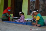 Guru kelas 1 SDN Sumberaji 2, Rini Harianti melakukan pembelajaran tatap muka di Dusun Ngapus, Desa Sumberaji, Kecamatan Kabuh, Kabupaten Jombang, Jawa Timur, Sabtu (8/8/2020). Karena sulitnya akses jaringan internet untuk belajar daring, pihak sekolah setempat berinisiatif mendatangi siswa kelas 1 dan 2 untuk mendapatkan pelajaran secara tatap muka dengan tetap menerapkan protokol kesehatan. Antara Jatim/Syaiful Arif/zk.
