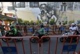 Personel Satpol PP Kota Denpasar berjaga di samping sekat pembatas jalan yang dipasang di kawasan Pasar Pemeregan, Denpasar, Bali, Minggu (9/8/2020). Pemasangan sekat pembatas jalan tersebut untuk mencegah pedagang berjualan kembali di bahu jalan yang menyebabkan kerumunan sebagai upaya memutus penyebaran COVID-19 di pasar tradisional tersebut. ANTARA FOTO/Nyoman Hendra Wibowo/nym.