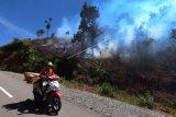 Pengendara melintas saat terjadi kebakaran lahan, di Kerinci, Jambi, Sabtu (8/8/2020). Gubernur Jambi Fachrori Umar menyebutkan sebanyak 258 desa di sejumlah kabupaten di provinsi itu berstatus daerah rawan kebakaran hutan dan lahan (karhutla). ANTARA FOTO/Wahdi Septiawan/hp.