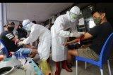 Petugas medis mengambil sampel darah pesepak bola Persik Kediri Jefferson Alves Olivira (kiri) dan ofisial tim Persik Kediri saat tes cepat (rapid test) COVID-19 di Kota Kediri, Jawa Timur, Senin (10/8/2020). Manajemen Persik Kediri mengadakan tes cepat kepada seluruh pemain dan ofisial tim sebelum menggelar latihan secara resmi menjelang digulirkannya kembali kompetisi Liga 1. ANTARA FOTO/Prasetia Fauzani/nym.