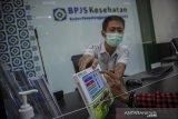 Petugas melayani warga di Kantor Cabang BPJS Kesehatan Bandung, Jawa Barat, Senin (10/8/2020). Menghadapi Adaptasi Kebiasaan Baru (AKB), BPJS Kesehatan menerapkan inovasi kemudahan layanan administrasi kepesertaan JKN-KIS melalui aplikasi Mobile JKN, Chika, Vika guna meminimalisir kunjungan peserta ke kantor cabang sebagai antisipasi penyebaran COVID-19. ANTARA JABAR/Raisan Al Farisi/agr