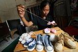 Perajin memasang tali pada sepatu rajut balita buatannya di Desa Tunglur, Kediri, Jawa Timur, Selasa (11/8/2020). Sepatu rajut seharga Rp30 ribu hingga Rp65 ribu per pasang tergantung jenis dan ukuran tersebut dipasarkan secara daring. Antara Jatim/Prasetia Fauzani/zk