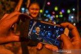 Warga berswafoto dengan latar belakang lampu lampion di Lembur Situ, Kabupaten Ciamis, Jawa Barat, Selasa (11/8/2020). Pernak-pernik seperti lampion, bendera, dan umbul-umbul yang dibuat dari hasil kreasi masyarakat secara gotong royong tersebut dipasang disepanjang jalan dalam rangka memeriahkan perayaan HUT ke-75 Kemerdekaan Republik Indonesia. ANTARA JABAR/Adeng Bustomi/ agr