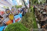 Sejumlah buruh yang tergabung dalam Aliansi Pekerja Buruh Banua Kalimantan Selatan berunjuk rasa di depan Gedung DPRD Kalsel di Banjarmasin, Kalimantan Selatan, Rabu (12/8/2020). Mereka selain menolak pengesahan RUU Omnibus Law Cipta Kerja karena dinilai dapat merugikan kaum buruh juga menuntut pencabutan Perpres tentang kenaikan iuran BPJS Kesehatan. Foto Antaranews Kalsel/Bayu Pratama S.