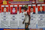 Warga melintas di depan alat peraga kampanye Pemilihan kepala desa (Pilkades) di Desa Panyingkiran, Kabupaten Ciamis, Jawa Barat, Rabu (12/8/2020). Kementerian Dalam Negeri (Kemendagri) memutuskan menunda pilkades serentak dan Pemilihan kepala Desa Antar Waktu (PAW) di seluruh Indonesia akibat COVID-19, tetapi Pilkades serentak di 143 desa di Ciamis tetap akan digelar pada 15 Agustus 2020. ANTARA JABAR/Adeng Bustomi/agr