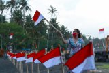 Pengunjung berada di pantai yang dipasang bendera merah putih oleh Kelompok Sadar Wisata (pokdarwis) di Pantai Cacalan, Banyuwangi, Jawa Timur, Jumat (14/8/2020). Pemasangan bendera merah putih untuk mempercantik kawasan wisata  pantai itu, bertujuan untuk menyemarakkan HUT ke-75 Kemerdekaan Indonesia. Antara Jatim/Budi Candra Setya/zk.