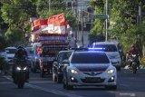 Polisi mengawal mobil berbendera Merah Putih yang dikendarai oleh Iyon Haryono (52) di Jalan Pahlawan Surabaya, Jawa Timur, Jumat (21/8/2020). Aksi memperingati HUT ke-75 Kemerdekaan Republik Indonesia dengan mengendarai mobil berbendera Merah Putih dari kota Bandung menuju Bali itu telah tiba di Surabaya. Antara Jatim/Didik/Zk