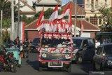 Mobil berbendera Merah Putih yang dikendarai oleh Iyon Haryono (52) melintas di Jalan Garuda, Surabaya, Jawa Timur, Jumat (21/8/2020). Aksi memperingati HUT ke-75 Kemerdekaan Republik Indonesia dengan mengendarai mobil berbendera Merah Putih dari kota Bandung menuju Bali itu telah tiba di Surabaya. Antara Jatim/Didik/Zk
