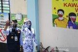 Gubernur Jawa Barat Ridwan Kamil (kiri) didampingi istri Atalia Praratya (kanan) berjalan menuju puskesmas Garuda di kecamatan Andir, Bandung, Jawa Barat, Selasa (25/8/2020). Ridwan Kamil akan menjalani sejumlah tes kesehatan dan tes usap atau swab test sebelum dilakukan proses penyuntikkan atau uji klinis tahap III vaksin Sinovac COVID-19. ANTARA JABAR/M Agung Rajasa/agr