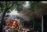 Petugas Dinas Pemadam Kebakaran memadamkan toko elektronik yang terbakar di Jalan Kranggan, Surabaya, Jawa Timur, Minggu (30/8/2020). Sekitar 22 kendaraan pemadam kebakaran dikerahkan untuk memadamkan kebakaran yang menewaskan lima orang di dalam toko tersebut. ANTARA FOTO/Didik Suhartono/nym
