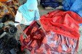 Perajin menyelesaikan proses pembuatan batik tulis di Desa Klampar, Pamekasan, Jawa Timur, Rabu (2/9/2020). Perajin batik di daerah itu, mengaku sejak diberlakukannya new normal, produksi batik meningkat dari sebelumnya 150 potong menjadi 180 potong atau naik sekitar 25 persen per pekannya, karena meningkatnya permintaan dari sejumlah daerah. Antara Jatim/Saiful Bahri/zk