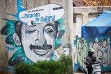 Pengendara melintas di dekat mural tentang aktivis HAM Munir Said Thalib di Jakarta, Senin (7/9/2020). Mural tersebut dibuat untuk mengenang mendiang pejuang kemanusiaan Munir Said Thalib yang meninggal dunia setelah diracun dalam penerbangan menuju Amsterdam, Belanda pada 7 September 2004, 16 tahun silam. ANTARA FOTO/Rivan Awal Lingga/wsj.