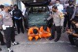 Kapolres Tulungagung AKBP Eva Guna Pandia (kiri) menunjukkan tersangka berikut barang bukti minuman keras sitaan saat gelar ungkap perkara, di Mapolres Tulungagung, Tulungagung, Jawa Timur, Selasa (8/9/2020). Sebanyak 509 botol minuman keras jenis ciu ukuran 500 ml dan 1.500 ml asal Sukaharja, Jawa Tengah berhasil diamankan dari empat tersangka pengedar, dua di antaranya ditangkap dalam operasi sergap mobil saat melintas dalam kota setempat. ANTARA FOTO/Destyan Sujarwoko/hp.