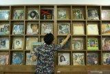 Pegawai RRI Surabaya menata piringan hitam album lagu lawas di Ruang Restorasi Piringan Hitam di RRI Surabaya, Jawa Timur, Jumat (11/9/2020). Lembaga Penyiaran Publik (LPP) Radio Republik Indonesia (RRI) Surabaya yang memiliki sekitar 8.000  piringan hitam album lagu dari masa ke masa tersebut telah melakukan restorasi atau merekam ulang menjadi digital sebanyak 3.000 piringan hitam album lagu sedangkan selebihnya rusak termakan usia. Antara Jatim/Didik/Zk