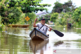 Seorang warga mendayung perahu melintasi banjir di kawasan Teluk Barak, Putussibau Selatan, Kabupaten Kapuas Hulu, Kalimantan Barat, Minggu (13/9/2020). Badan Penanggulangan Bencana Daerah Kapuas Hulu menyatakan berdasarkan data per hari Minggu (13/9/2020) terdapat seratus rumah warga di lima kecamatan yaitu Putussibau Utara, Putussibau Selatan, Bika, Kalis dan Embaloh Hilir di kabupaten setempat yang terendam banjir akibat tingginya curah hujan selama beberapa hari terakhir. ANTARA FOTO/Jessica Helena Wuysang/aww.