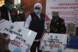 Gubernur Jawa Timur Khofifah Indar Parawansa (tengah) menyerahkan Bantuan Langsung Tunai Dana Desa (BLT DD) kepada warga di kantor Bakorwil Pamekasan, Jawa Timur, Senin (14/9/2020). Dalam kesempatan itu Khofifah menyerahkan bantuan ventilator kepada RSUD Bangkalan, Sampang dan Sumenep, serta 8.000 masker untuk Korkab PKH, TKSK, Tagana dan  Bantuan Langsung Tunai Dana Desa (BLT DD) serta BUMDes. Antara Jatim/Saiful Bahri/zk.