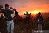 Wisatawan lokal menikmati matahari terbenam (sunset) dibukit singgah mata, Kabupaten Aceh Barat Daya, Aceh, Ahad (13/9). Bukit singgah mata dengan ketinggian 1000 kaki tersebut terletak di kilometer 21 jalan Ie Mirah, Babahrot-Terangun, Gayo Lues menjadi alternatif menikmati matahari terbenam dengan pemandangan puncak pengunungan. Antara Aceh/Suprian.