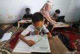 Seorang guru sekolah dasar mengajar di rumah muridnya di Kelurahan Pesantren, Kota Kediri, Jawa Timur, Selasa (15/9/2020). Pembelajaran kelompok kecil di rumah siswa sekali dalam sebulan tersebut sebagai evaluasi penguasan materi pelajaran sekaligus upaya penyegaran agar siswa tidak bosan mengikuti pembelajaran jarak jauh. Antara Jatim/Prasetia Fauzani/zk