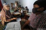 Dua orang guru sekolah dasar mengajar di rumah muridnya di Kelurahan Pesantren, Kota Kediri, Jawa Timur, Selasa (15/9/2020). Pembelajaran kelompok kecil di rumah siswa sekali dalam sebulan tersebut sebagai evaluasi penguasan materi pelajaran sekaligus upaya penyegaran agar siswa tidak bosan mengikuti pembelajaran jarak jauh. Antara Jatim/Prasetia Fauzani/zk