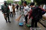 Dandim 0101/BS Letkol Inf Abdul Razak (kiri), Ketua DPRK Farid Nyak Umar (dua kiri) dan Wali Kota Banda Aceh Aminullah Usman (tiga kiri) menyaksikan warga menjalani sanksi sosial menyapu jalan akibat tidak memakai masker di Banda Aceh, Aceh, Selasa (15/9/2020). Pemerintah Kota Banda Aceh mulai menerapkan sanksi denda Rp100 ribu atau sanksi sosial seperti menyapu jalan, membersihkan rumah ibadah dan mengumandang azan bagi warga yang terjaring razia masker. Antara Aceh/Irwansyah Putra.