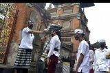 Pecalang atau petugas pengamanan adat Bali memeriksa suhu tubuh umat Hindu yang akan bersembahyang saat Hari Raya Galungan di Pura Jagatnatha, Denpasar, Bali, Rabu (16/9/2020). Perayaan Hari Raya Galungan yang merupakan hari kemenangan kebenaran (Dharma) atas kejahatan (Adharma) tersebut diikuti umat Hindu di Pulau Dewata dengan tetap menerapkan protokol kesehatan secara ketat untuk mencegah penyebaran pandemi COVID-19. ANTARA FOTO/Fikri Yusuf/nym.
