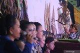 Dalang muda Megan Yosa Pratama (kanan) memaikan wayang kulit dengan lakon Wahyu Cakraningrat yang disiarkan secara daring di Kota Kediri, Jawa Timur, Rabu (16/9/2020). Pagelaran wayang kulit kolaborasi dua dalang muda, satu dalang cilik, dan sejumlah sinden cilik tersebut diselenggarakan pemerintah daerah setempat guna mengapresiasi dan mendorong regenerasi pelaku kesenian tradisional wayang kulit. Antara Jatim/Prasetia Fauzani/zk