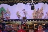 Dalang muda Megan Yosa Pratama memaikan wayang kulit dengan lakon Wahyu Cakraningrat yang disiarkan secara daring di Kota Kediri, Jawa Timur, Rabu (16/9/2020). Pagelaran wayang kulit kolaborasi dua dalang muda, satu dalang cilik, dan sejumlah sinden cilik tersebut diselenggarakan pemerintah daerah setempat guna mengapresiasi dan mendorong regenerasi pelaku kesenian tradisional wayang kulit. Antara Jatim/Prasetia Fauzani/zk
